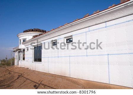 A home at a new construction site is layered with insulating foam before the stucco is added.  Ideal for new home construction advertising and other home construction promotional inferences.