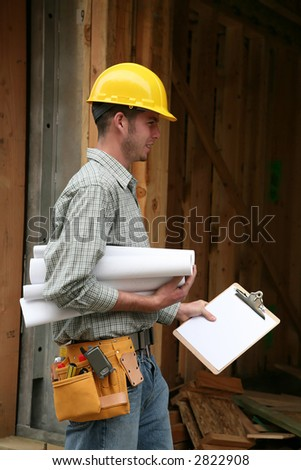 A home contractor holding blueprints outside a home in progress