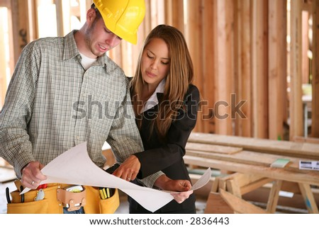 A Home Designer Working With A Home Builder And Inspecting The