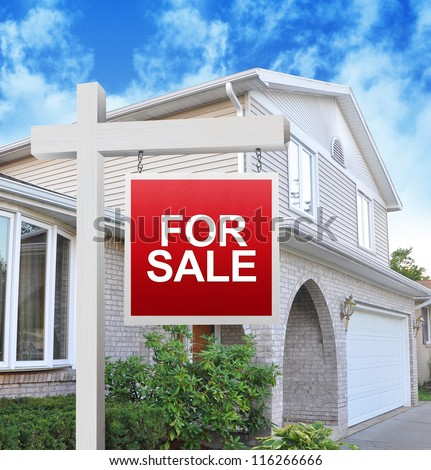 A home is advertising a for sale sign on a wooden sign post in red. Use it for a housing market concept. stock photo