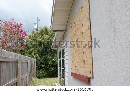 A home with plywood covering the window in preparation for a hurricane.  The storm clouds are gathering in the sky.  Horizontal view.