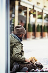 A homeless guy is sitting in the ground with a dog in his feet. He is begging for money in the streets. The man is unidentified. The image has a vintage effect applied.
