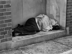 A Homeless Man bundled up under a jacket asleep in a city doorway