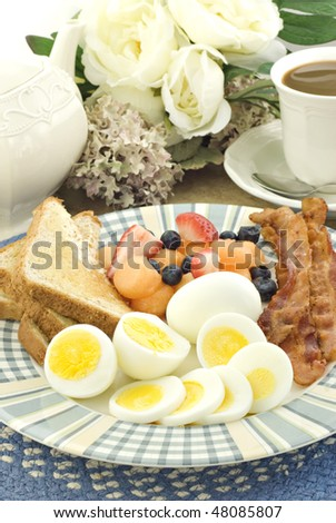 A homemade bacon and hard boiled egg breakfast, with hot coffee, vertical
