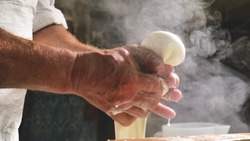 A homemade cheese producer, produces handmade mozzarella with fresh quality milk from her cows sheep in the morning. Concept of: tradition, italy, mozzarella.