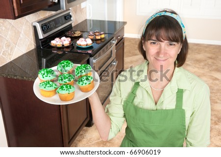 A homemaker displays a set of green cupcakes with clover sprinkles in her kitchen.