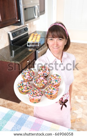 A homemaker shows off her decorated cupcakes with pink icing and candy sprinkles.  Focus is on the cupcakes.