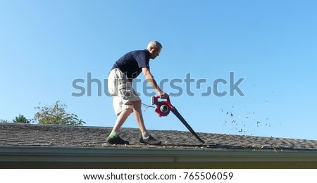 A homeowner is on the roof of his residence using a leaf blower to remove leaves from the gutter in preparation for storm season water runoff. Stock photo ©
