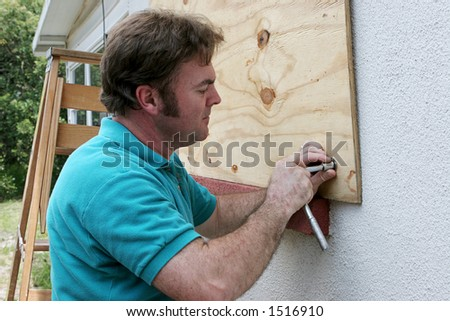 A homeowner or handy man screwing plywood onto windows in preparation for a hurricane.