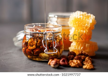A honey jar with a spoon for honey and nuts on a dark background. Selective focus