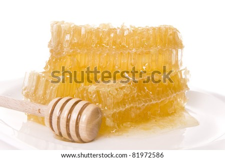 A honeycomb pile with a wooden stick isolated on white