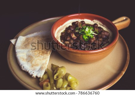 A horizontal color studio image of Egyptian, Arabian, Middle Eastern Traditional food (Fava Beans with Tahini) A.K.A (Foul) - Also served in Lebanon and most of Arabian countries. #786636760