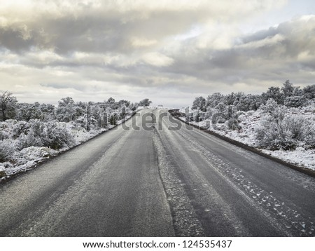 A horizontal image of a black and white asphalt long road