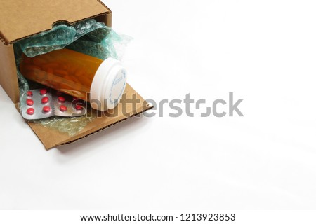 A horizontal image of a box of compounded prescription medications shipped from a mail order pharmacy (white background).  Room for text (copy) #1213923853