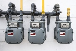A horizontal image of natural gas meters hanging outside on a white wall of a building.