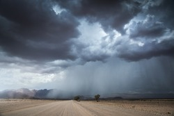 A horizontal landscape photograph of a road leading to a massive dramatic rain and thunder storm with mountains in the distance in the dry Namib Desert near Sesriem and Sossusvlei.