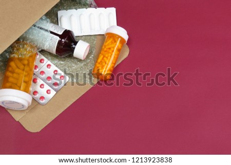 A horizontal, overhead (top down) image of a box of compounded prescription medications shipped from a mail order pharmacy with a red background.  Room for text (copy) #1213923838