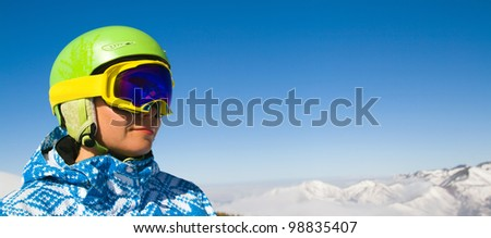 A horizontal panorama with a portrait of a female snowboarder wearing a helmet with a bright reflection in the glasses on the background of high snow-capped Alps in Grindelwald, Swiss