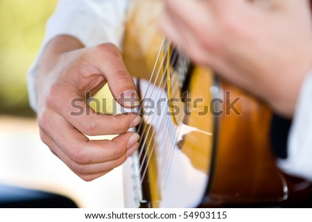 A horizontal photo of a caucasian musician playing a classical guitar at a wedding reception