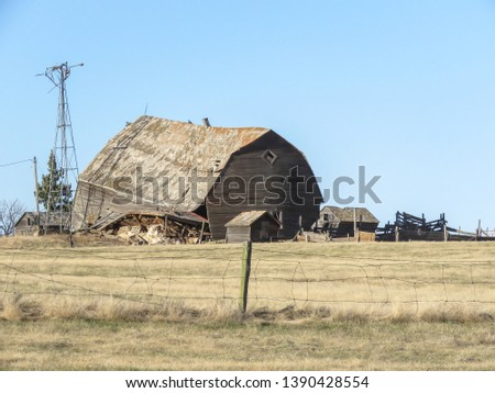 A horizontal photo of a old barn caving in.