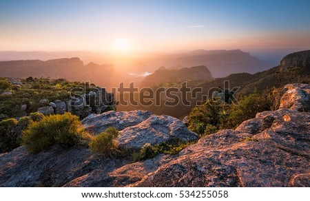 A horizontal photograph of a beautiful sunset over the Blyde River Canyon taken from Mariepskop