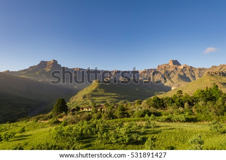 A horizontal photograph of a low angle view of the tranquil Amphitheatre in the Royal Natal National Park in the Drakensberg mountains with early morning sun rays shining over the valley at sunrise