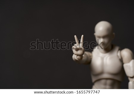 A horizontal portrait of mannequin showing v-sign against black background Stock photo ©