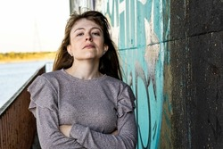 A horizontal shot of a Hispanic woman with her head up and arms crossed; graffiti wall background