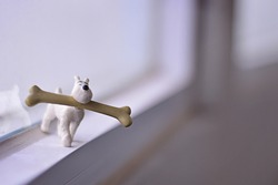 A horizontal shot of a toy dog holding a huge bone on a blurred background