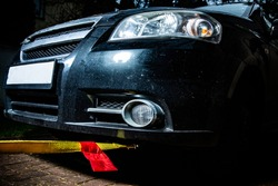 A horizontal view of a black automobile with yellow towline attached to a car towing eyelet. Towing a broken vehicle with a tow rope at night. Car assistance services.