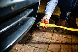 A horizontal view of a male hand in a glove attaching a towline to a car, selective focus. Towing a broken vehicle with a tow rope.