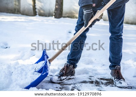 A horizontal view of shoveling snow from a sidewalk, a driveway with a lightweight, blue snow shovel, on a cold sunny day. Winter household chores during heavy snow.