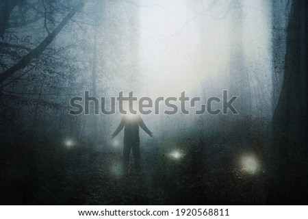 A horror concept of a figure with a glowing head with glowing orbs in a spooky forest on a moody, foggy winters day. With a grunge, abstract edit.