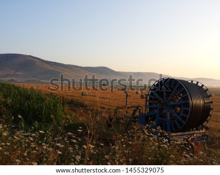 A hose-reel irrigation machine aside. A huge field with straw balls, spread all over a field in background. During the summer, Kozani, Greece. #1455329075