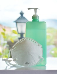 A hospital facemask and alcohol sanitizer for safety precautions against flu, coronavirus, cough, colds or other sicknesses