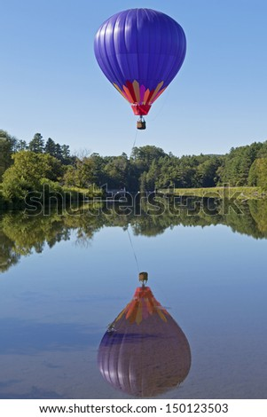 A hot air balloon and its reflection over a clear blue pond.