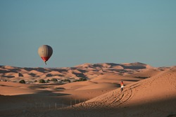 a hot air balloon flying over the desert