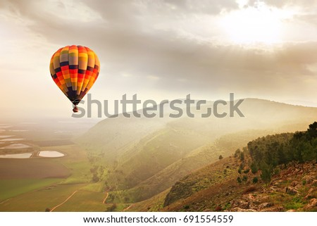 A Hot Air balloon in the mist sunlight over the mountains of Mount Gilboa, Israel. Adventure and travel - Shutterstock ID 691554559