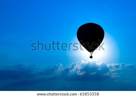 A hot air balloon is silhouetted against a bright blue sky as it eclipses the sun.