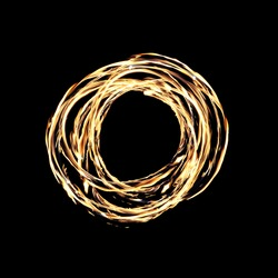 A hot circle of firey flames on a black background created by a fire dancer.
