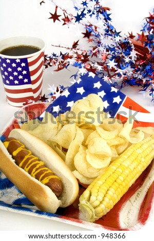 A hot dog, chips and corn on the cob are served with patriotic-themed decorations. - stock photo