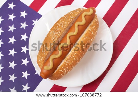 A Hot Dog in a bun with yellow mustard on a plate on American flag