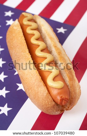 A Hot Dog in a bun with yellow mustard on an american flag.