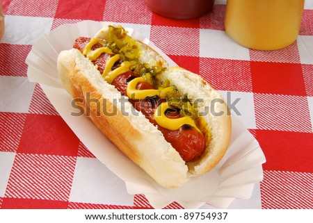 A hot dog with relish on a picnic table