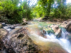 A hot spring merging with cold river creating a perfect temperature of water for a swim in Bajawa, Flores, Indonesia. Banks of the river are overgrown with trees. A lot of moss on the bottom
