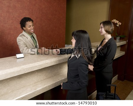 A hotel employee cheerfully welcomes guests. - stock photo