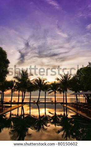 A hotel infinity pool in Thailand at sunrise with a paradise backdrop of palm trees and ocean. #80150602