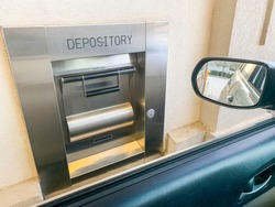 A 24-hour night depository terminal attached to the wall of a bank building.