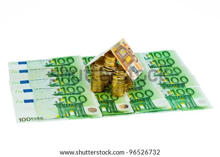 a house made of coins and banknotes. photo icon for house construction and home loans - stock photo