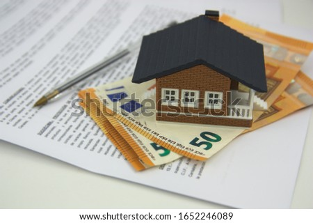 A house on some bills and some papers that look like a mortgage to sign or insurance to hire